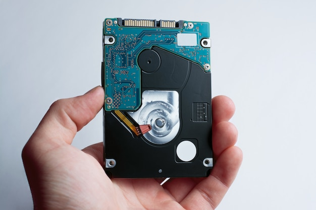 A hand holds hard disk drive against the white background