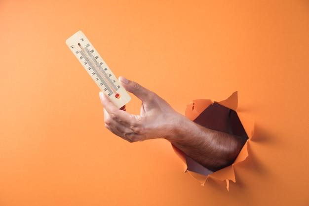 손 오렌지 배경에 집 온도계를 보유