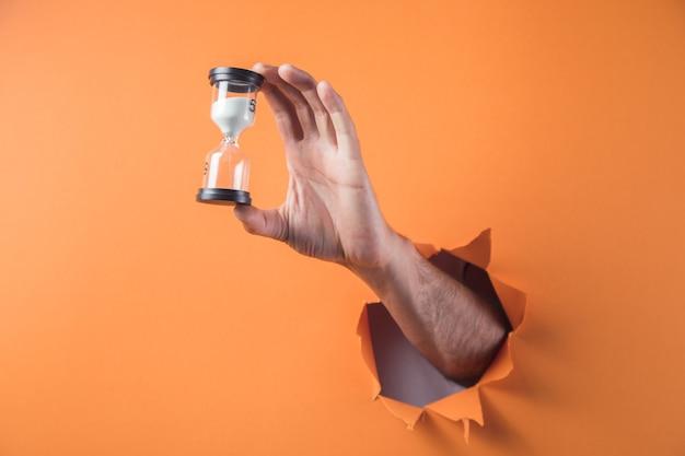 Рука держит песочные часы на оранжевом фоне
