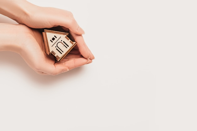 Hand holds house miniature model on white wall