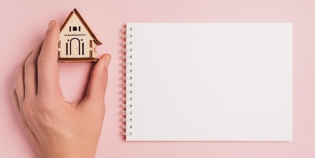 Рука держит миниатюрную модель дома с пустым фоном на розовом фоне. инвестиции, недвижимость, дом, жилье
