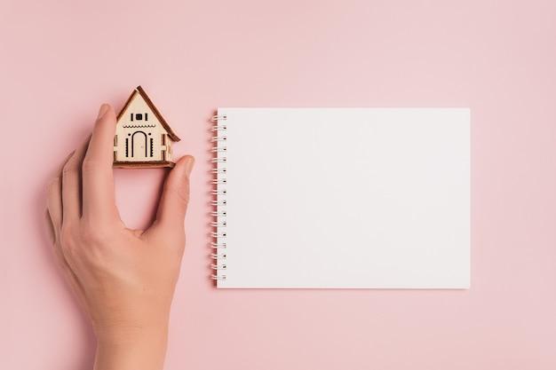 손 분홍색 배경에 빈 노트북 집 미니어처 모델을 보유하고있다. 투자, 부동산, 주택, 주택
