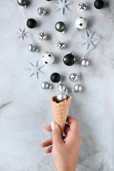手はさまざまなクリスマスの装飾が施されたアイスクリームワッフルコーンを保持します