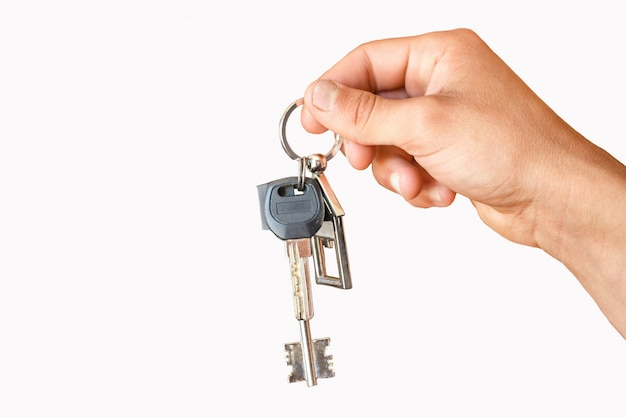 The hand holds the keys to the apartment or home