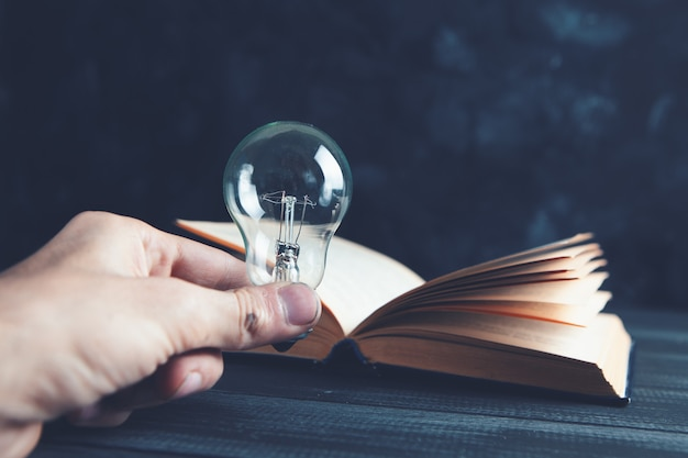 Hand holds a light bulb next to a book