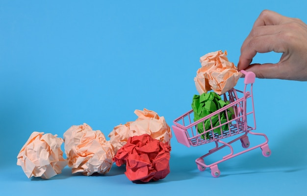 Hand holds a miniature metal cart with mint paper balls on a blue surface. concept for buying ideas, new creative ideas