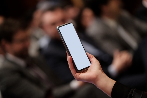 Hand holds a mobile phone in a meeting