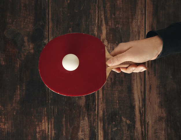 Hand holds one professional rocket above wooden aged table with ball on it and ready to play ping pong