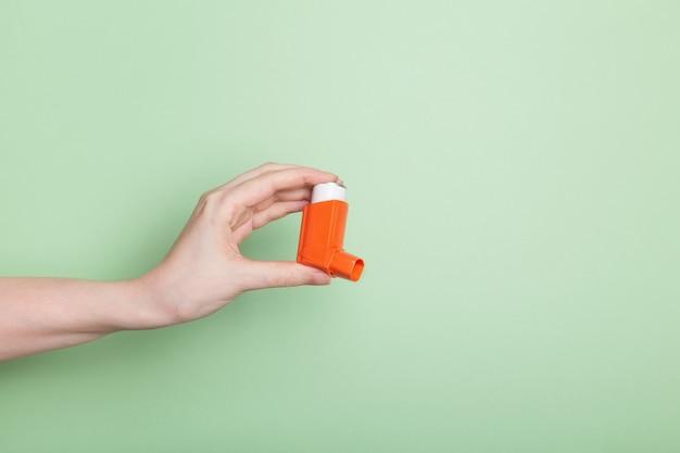 손은 밝은 녹색 배경에 고립 된 천식을 치료하기 위해 오렌지 흡입기를 보유하고 있습니다.