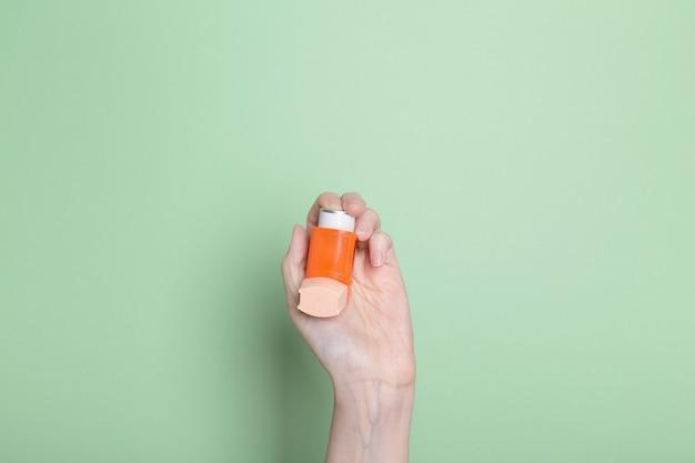 손은 밝은 녹색 배경에 천식을 치료하기 위해 오렌지 흡입기를 보유하고 있습니다.