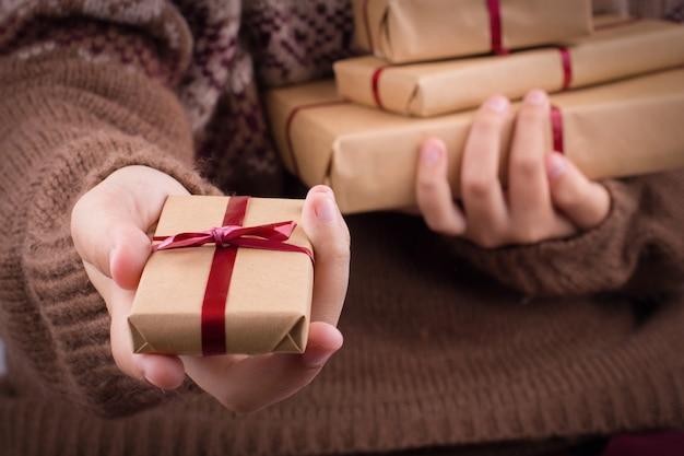 手はギフト用の箱を保持します。ニットセーターの女の子は、茶色のクラフトペーパーのギフトボックスのスタックを保持しています。