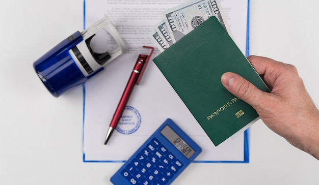 Hand holds out the green passport with us dollars on the background of documents and rubber stamp