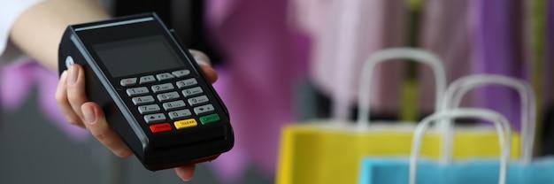 Рука протягивает терминал для оплаты кредитной картой