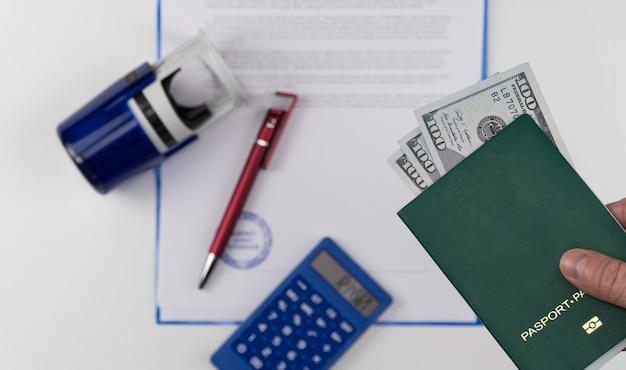 Рука протягивает зеленый паспорт с долларами сша на фоне документов и штампа