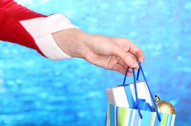 크리스마스 공 및 선물이 포함된 패키지를 손에 들고 있습니다.