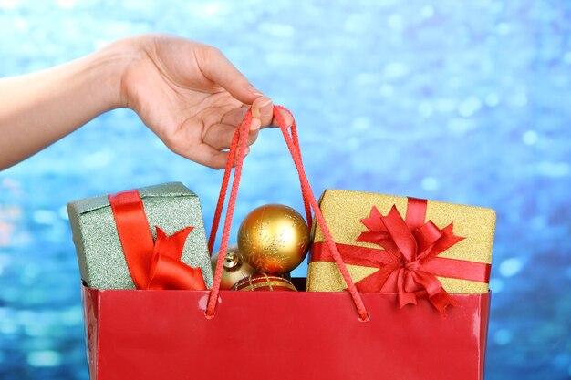 手はクリスマスボールとギフトのパッケージを保持します