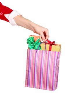 手は白い表面に分離された新年の贈り物とパッケージを保持します