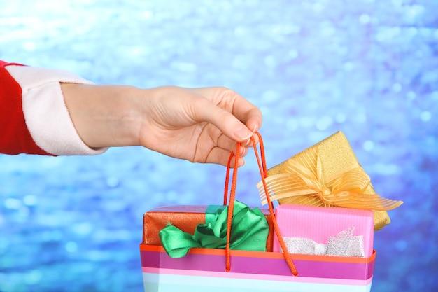 파란색 배경에 새해 선물이 있는 패키지를 손에 들고 있습니다.
