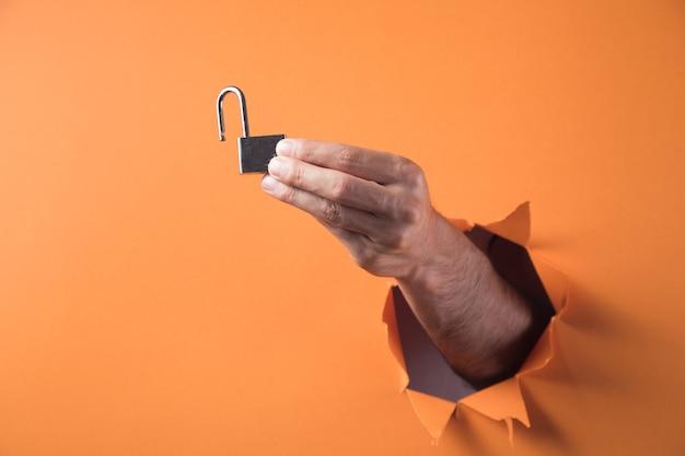 손 오렌지 배경에 자물쇠를 보유