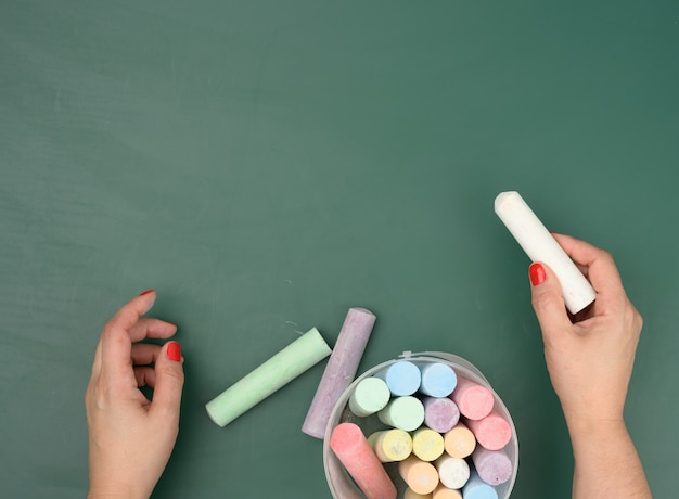 Hand holds a piece of white chalk on the background of an empty green chalk board, presentation concept, back to school