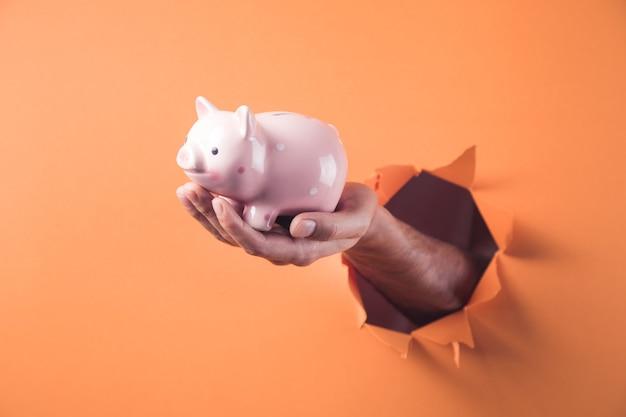 手はオレンジ色の背景に貯金箱を保持します