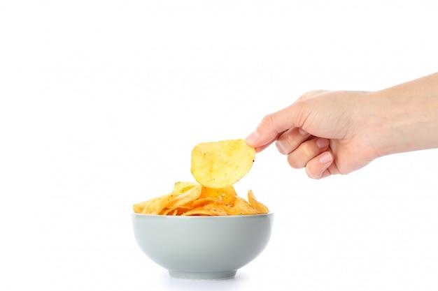 Рука держит картофельные чипсы, изолированные на белом, пространство для текста