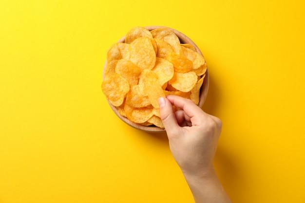 Рука держит картофельные чипсы на желтом, пространство для текста. вид сверху