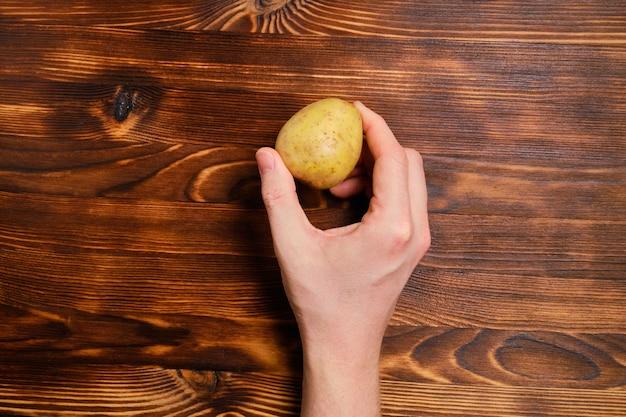 Рука держит картофель на дровах. вид сверху.
