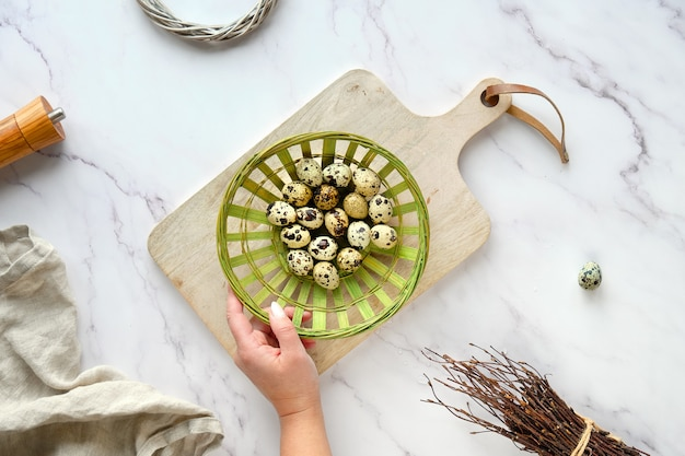 Hand holds rattan plate, basket with quail eggs