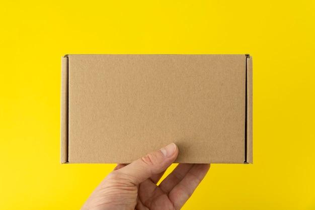 手は長方形の段ボール箱、黄色の背景を保持します。スペースをコピーします。モックアップ。
