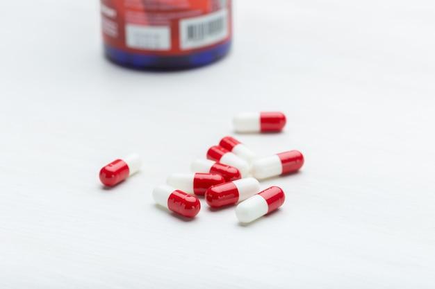 Рука держит красные и белые таблетки на фоне белого стола. понятие о лекарствах витаминов и микроэлементов. лечение и профилактика.