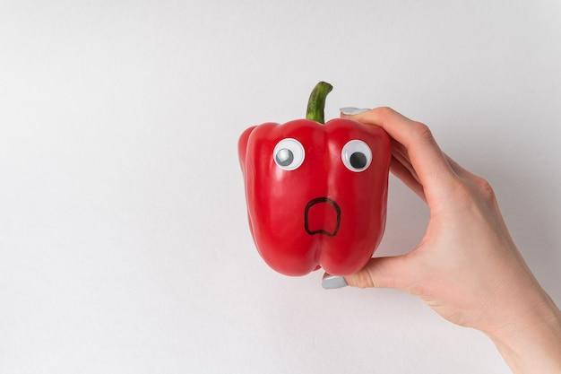 Рука держит красный перец колокольчика с googly глазами и испуганным смешным лицом. сырой сладкий перец на белом.