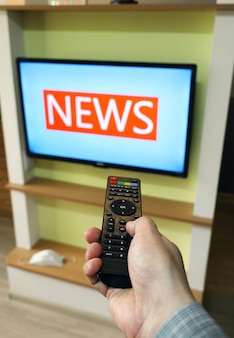 Hand holds the remote control and directs it to tv changing channel news