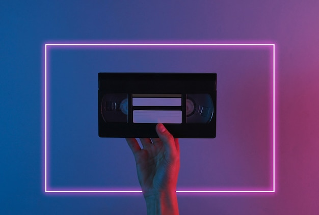 Hand holds retro video cassette with red blue neon light.