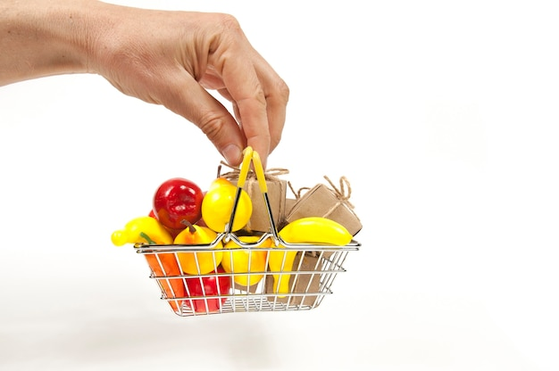 A hand holds a shopping basket full of fruit and gift boxes with bows on white