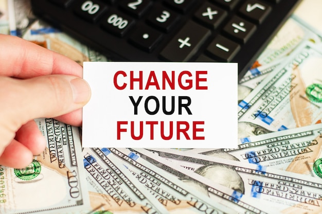 A hand holds a sign with the inscription - change your future on the background of banknotes and a calculator on the table