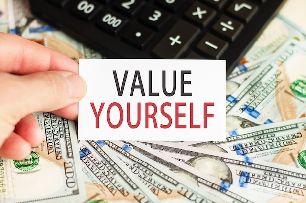 A hand holds a sign with the inscription - value yourself on the surface of banknotes and a calculator on the table