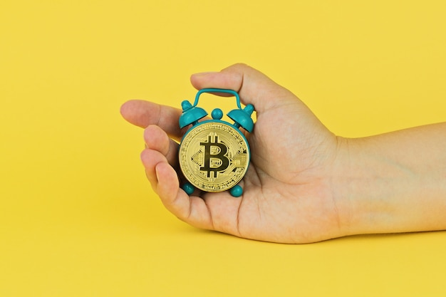 Hand holds small alarm clock with bitcoin