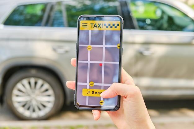 손은 응용 프로그램에서 택시 검색 버튼에 스마트 폰과 손가락 클릭을 보유하고 있습니다.