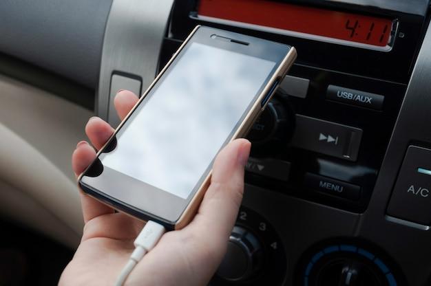 손은 플러그로 충전 된 자동차에 스마트 폰을 보유