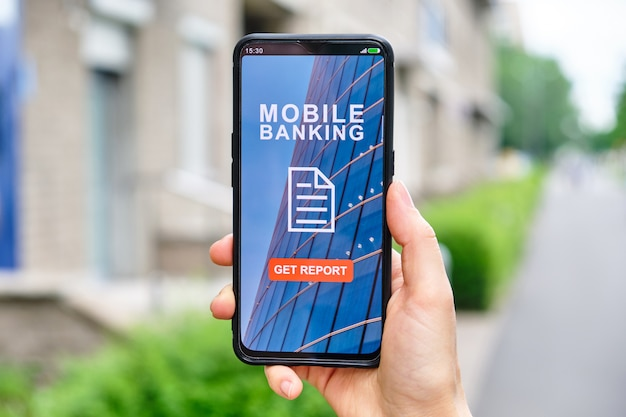 手は、モバイルバンキングインターフェイスを備えたスマートフォンを保持しており、クリックして金融取引に関するレポートを取得します。