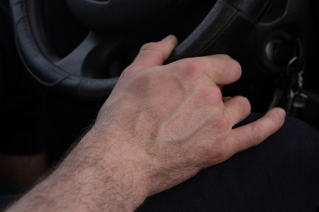 Hand holds the steering wheel of a car driving a car