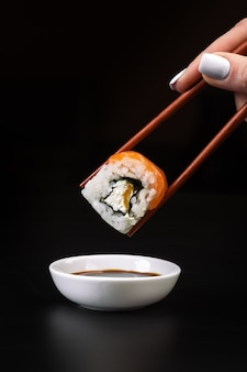 Hand holds sushi over bowl with soy sauce on black table.