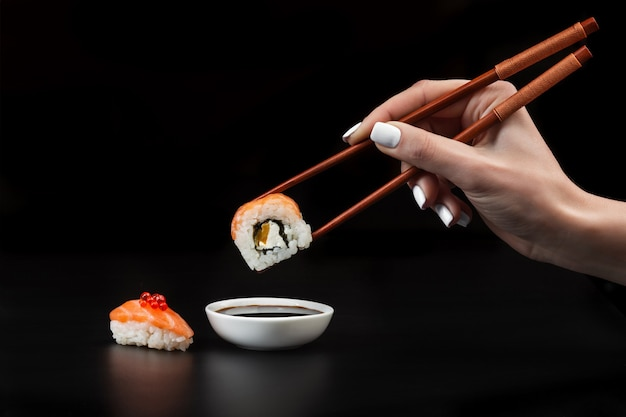 Рука держит суши над миской с соевым соусом на черном столе.