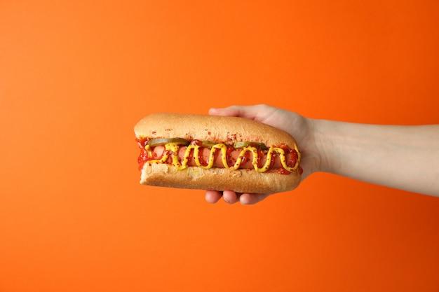 Hand holds tasty hot dog on orange