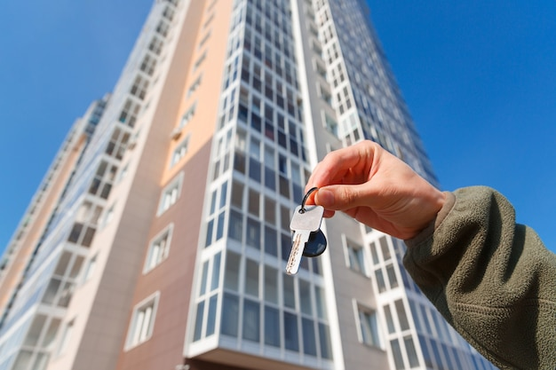 Рука держит ключи от новой квартиры