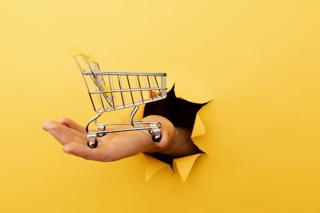 손을 구멍을 통해 노란색 종이 배경에 미니 식료품 쇼핑 트롤리를 보유합니다. 판매 또는 쇼핑 개념