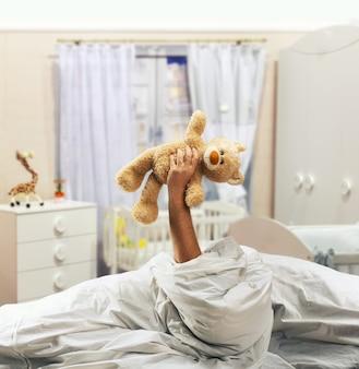 Рука держит игрушечного медведя над кроватью