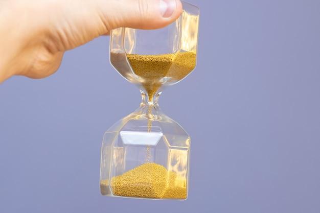 Рука держит прозрачные стеклянные песочные часы с падающим желтым золотым песком на синем фоне стены