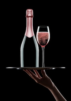 Hand holds tray with pink rose champagne bottle and glasses with bubbles on black background